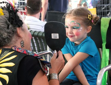 A young girl at Oktoberfest sees her newly painted face for the first time. She asked to be a flower for the day.